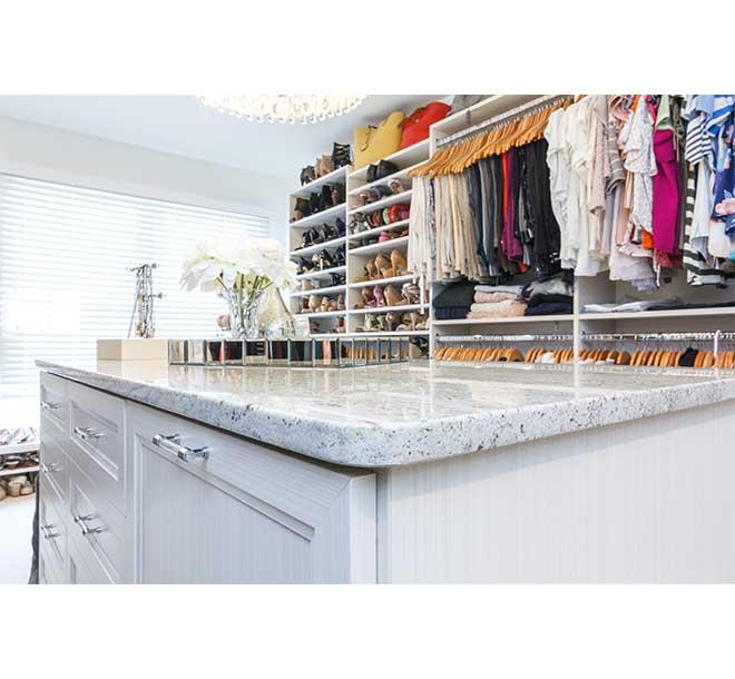 Center island with granite countertop in a custom built walk-in closet