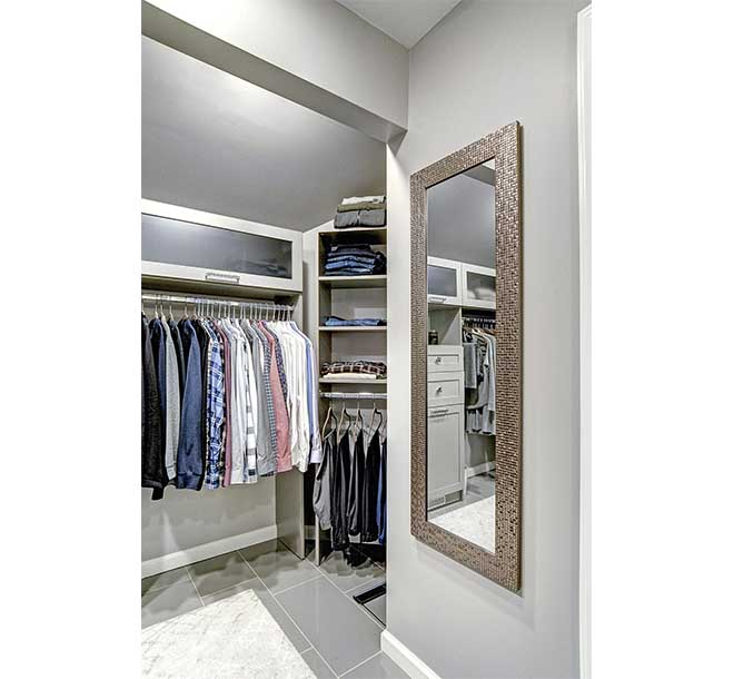Walk-in closet with corner shelving and mirror