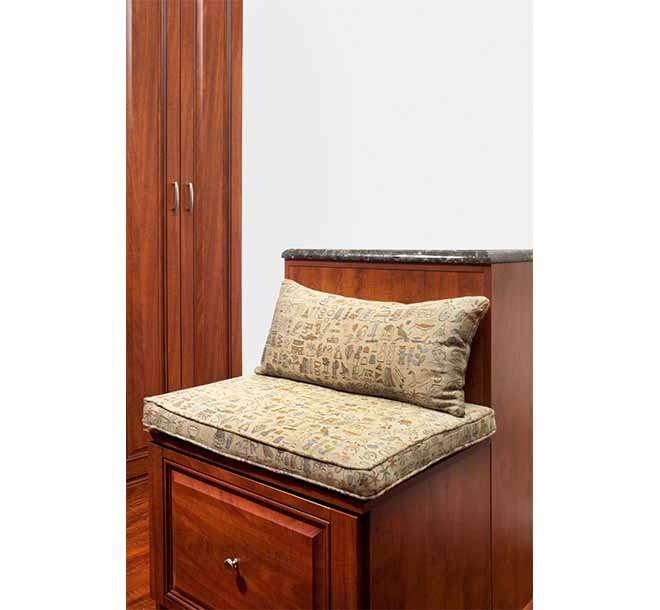 Wide walk-in closet center island with bench and pillow