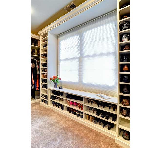 Shoe cubbies and shelves filled with footwear around large picture window