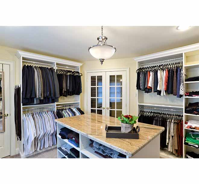 His and hers walk-In closet with granite top center island