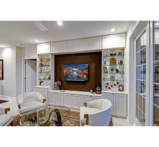 Wall unit designed with clear glass shelves and entertainment area