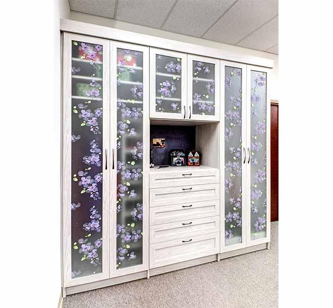 Custom wardrobe closet with beautiful glass door inserts and custom shelving