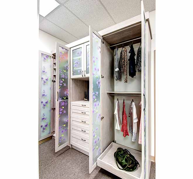 Wardrobe doors open to reveal clothing organized on hanging storage and shelves