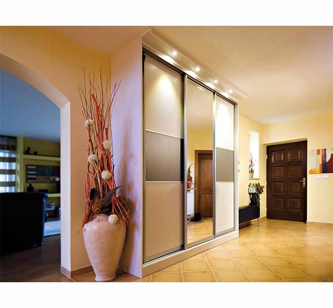 Custom wardrobe with sliding glass doors and built-in lighting