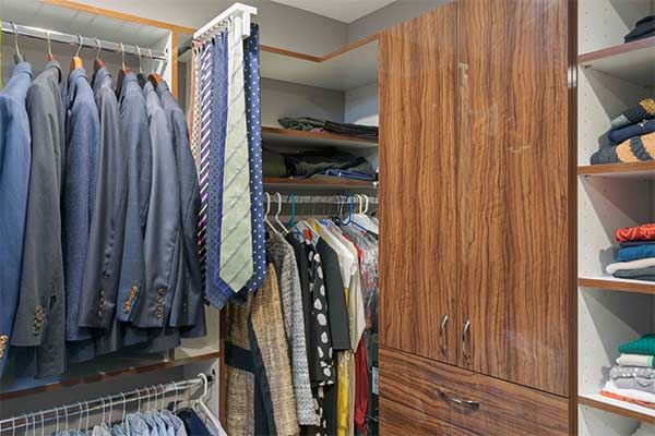 Closet with clothes and accessories like belts and ties neatly organized