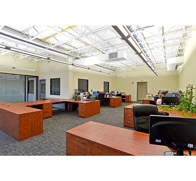 Custom commercial office design with consistent desk style and workspace areas