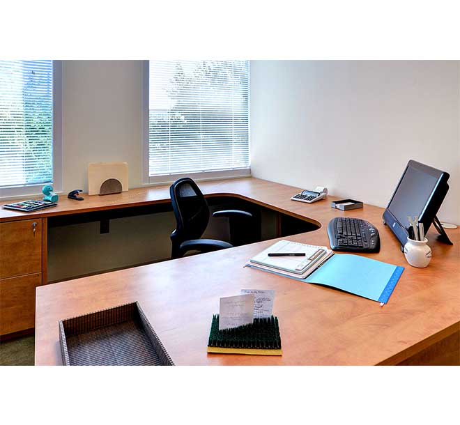 Commercial office designed with a wraparound desk and locked filing cabinets