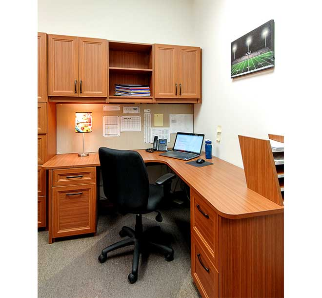 Custom commercial office space with desk and cabinets throughout