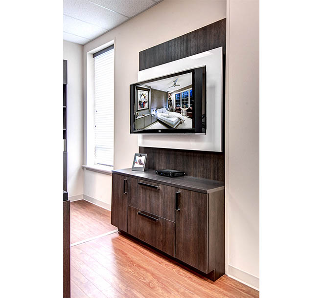 Custom built office cabinet with counter and tv mounted above
