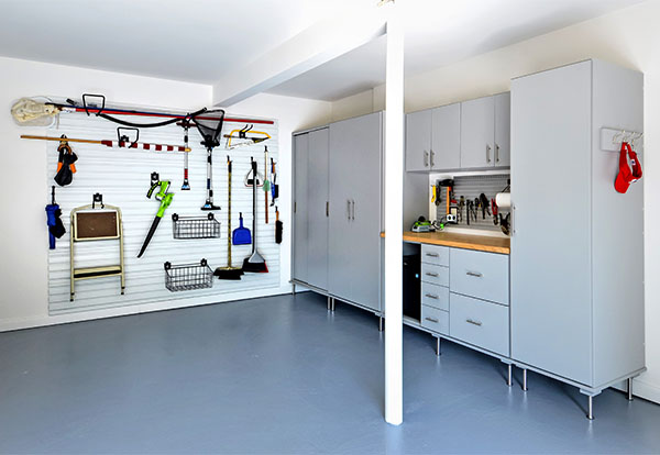 Garage neatly organized with cabinets and Storwall system