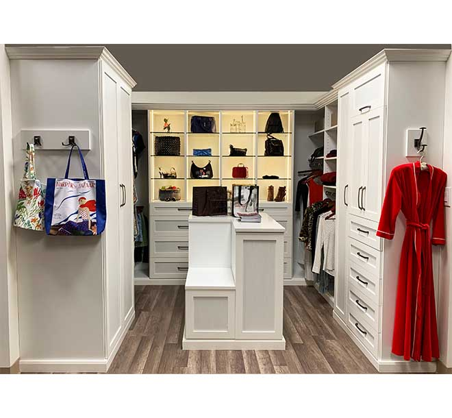 Custom white walk-in closet system with center island and cabinets