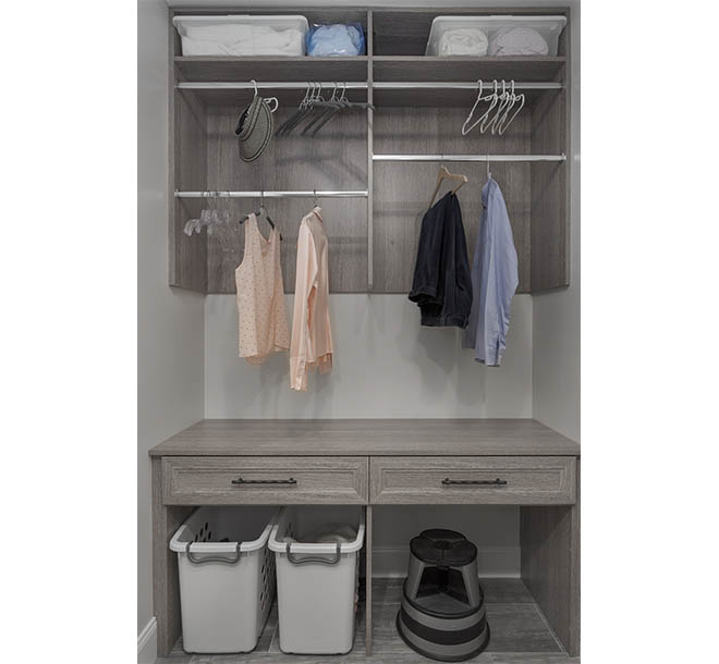 Custom laundry room cabinet with clothing items hung neatly
