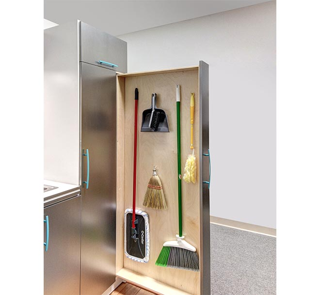 Mops and brooms stored on slide out vertical storage cabinet
