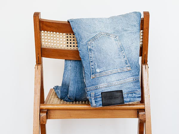 Blue jeans folded over chair