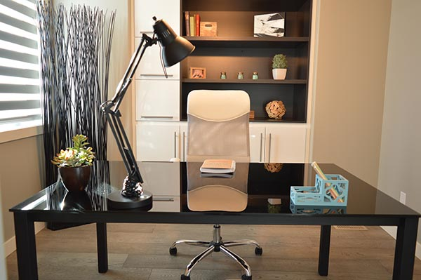 Beautiful home office with black desk with lamp and matching cabinet
