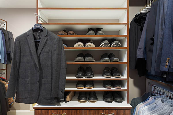Mens shoe collection neatly organized on shelves