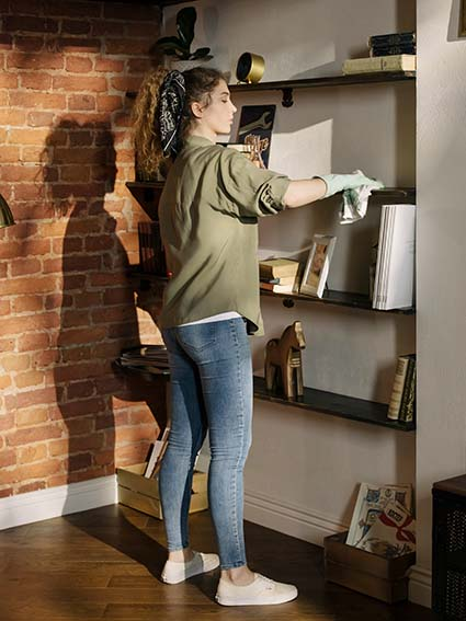 Woman spring cleaning the shelves on her bookcase