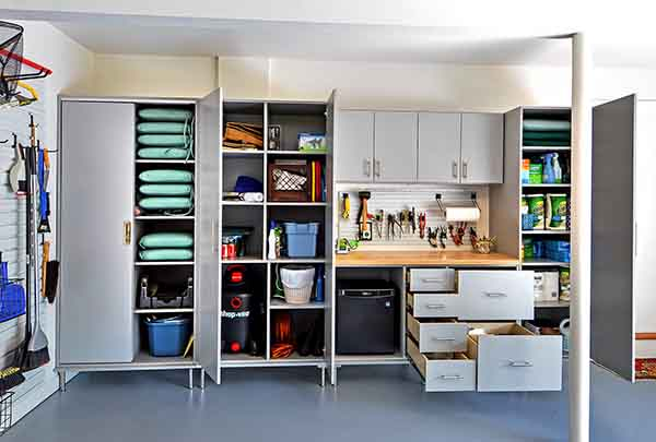 Grey garage cabinet and drawers open with organized outdoor gear