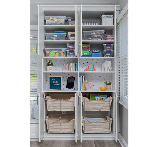 Custom shelves and sliding basket storage within a craft room cabinet