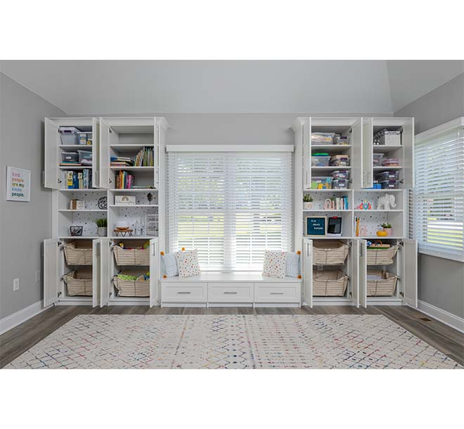 Custom wall unit cabinets with shelving neatly organizing playroom items