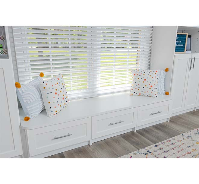 A bench underenath a window fram with additional drawers for storage underneath