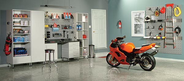 Motorcycle parked in clen and organized garage with custom cabinets