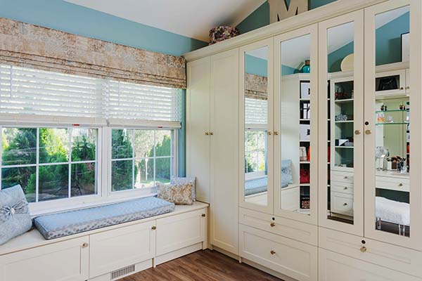 Bench seat under window with closet cabinets and mirrored doors