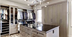 Walk-in closet with center island and custom cabinets and shelves