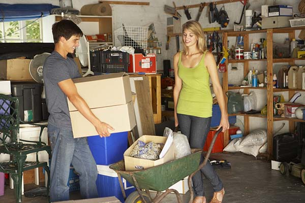 Brother and sister organizing and decluttering their garage