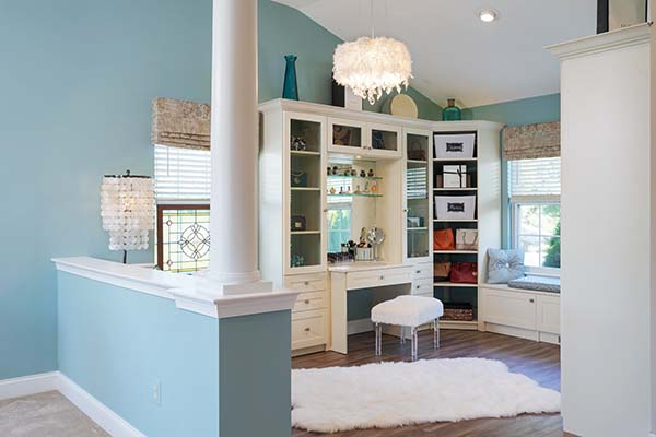 Walk in closet and sitting room with half wall and vanity