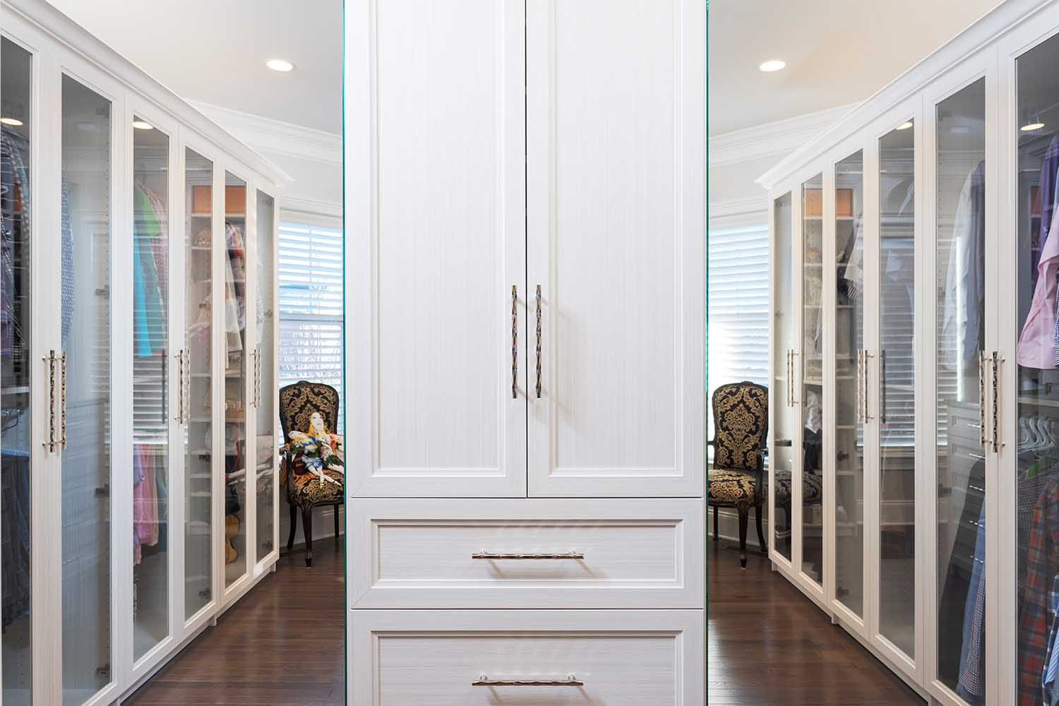 Transitional walk in wardrobe with glass doors organizing clothes on both sides