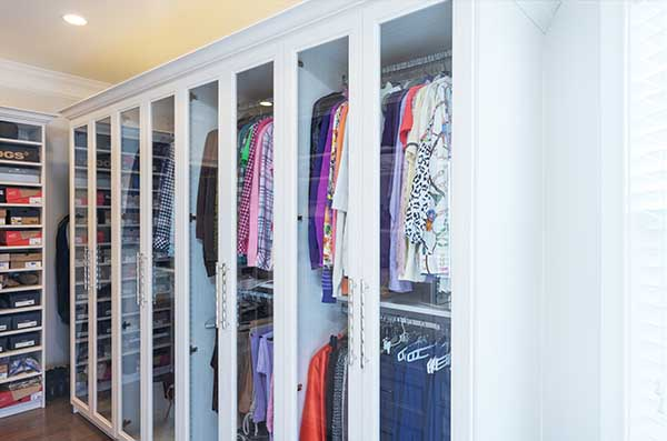 Clothes neatly organized on double hanging sections in custom wardrobe cabinet