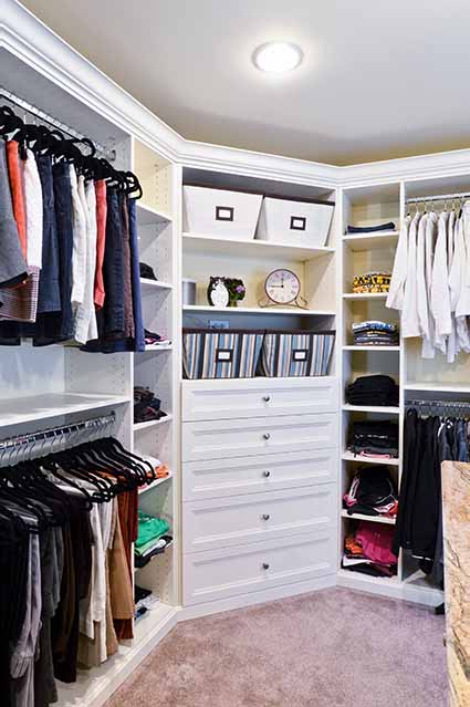 closet with double hangers, cubbies and custom shleves all with a white finish