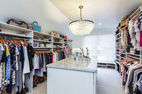 Walk in wardrobe with white granite top center island