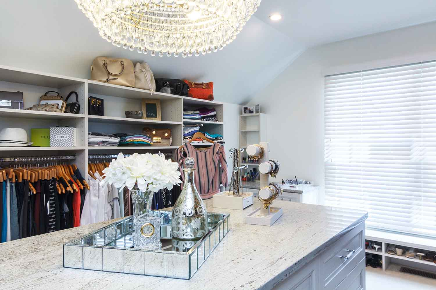 Chich walk in closet customized with shelving and center island