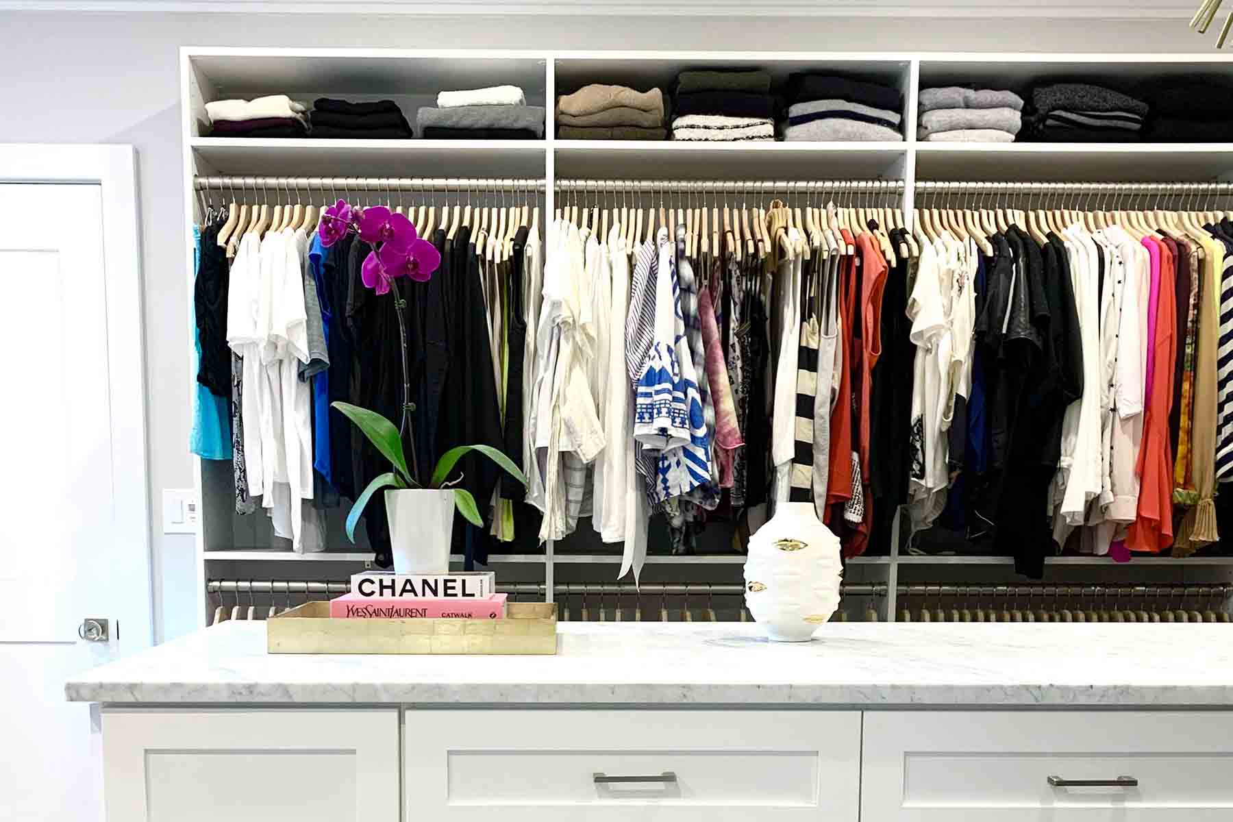 Walk-in Closet with hanging sections and center island with flowers