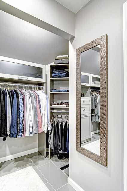 Custom closet corner with custom cabinets and flip-up storage on top