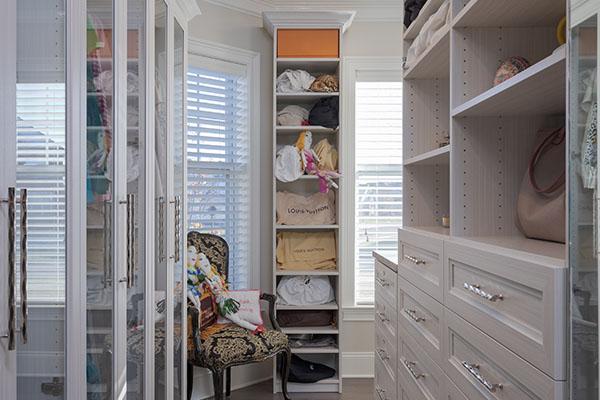 Walk-in closet with free standing custom built cabinet between windows