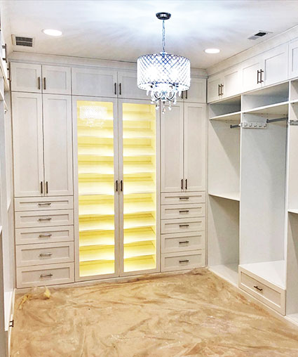 Walk in wardrobe with specialty lighting above and in shoe cabinets