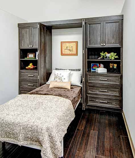 Bifold Murphy bed open with surrounding cabinetry