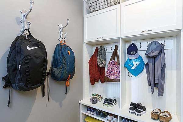 Organized mudroom with bags and jackets neatly hung on hooks