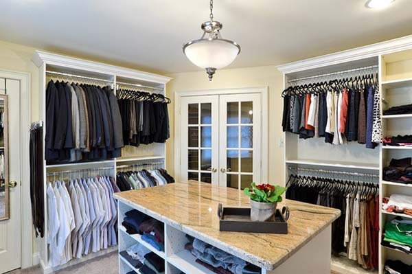 His and her walk-in closet with clothing organized on each side