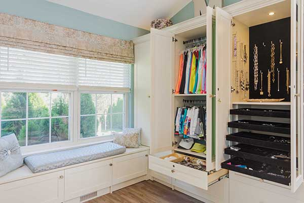 Cabinets organized with double hangers in luxury walk-in sitting room