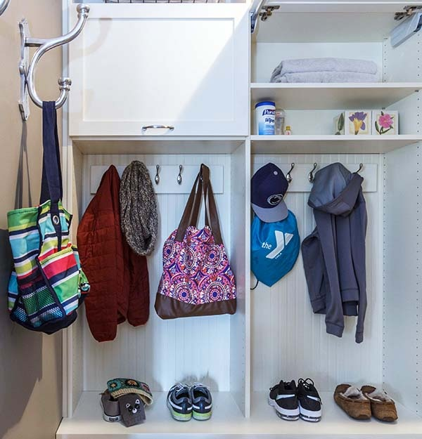 Mudroom neatly organized with bags hung on hooks and shoes in cubbies