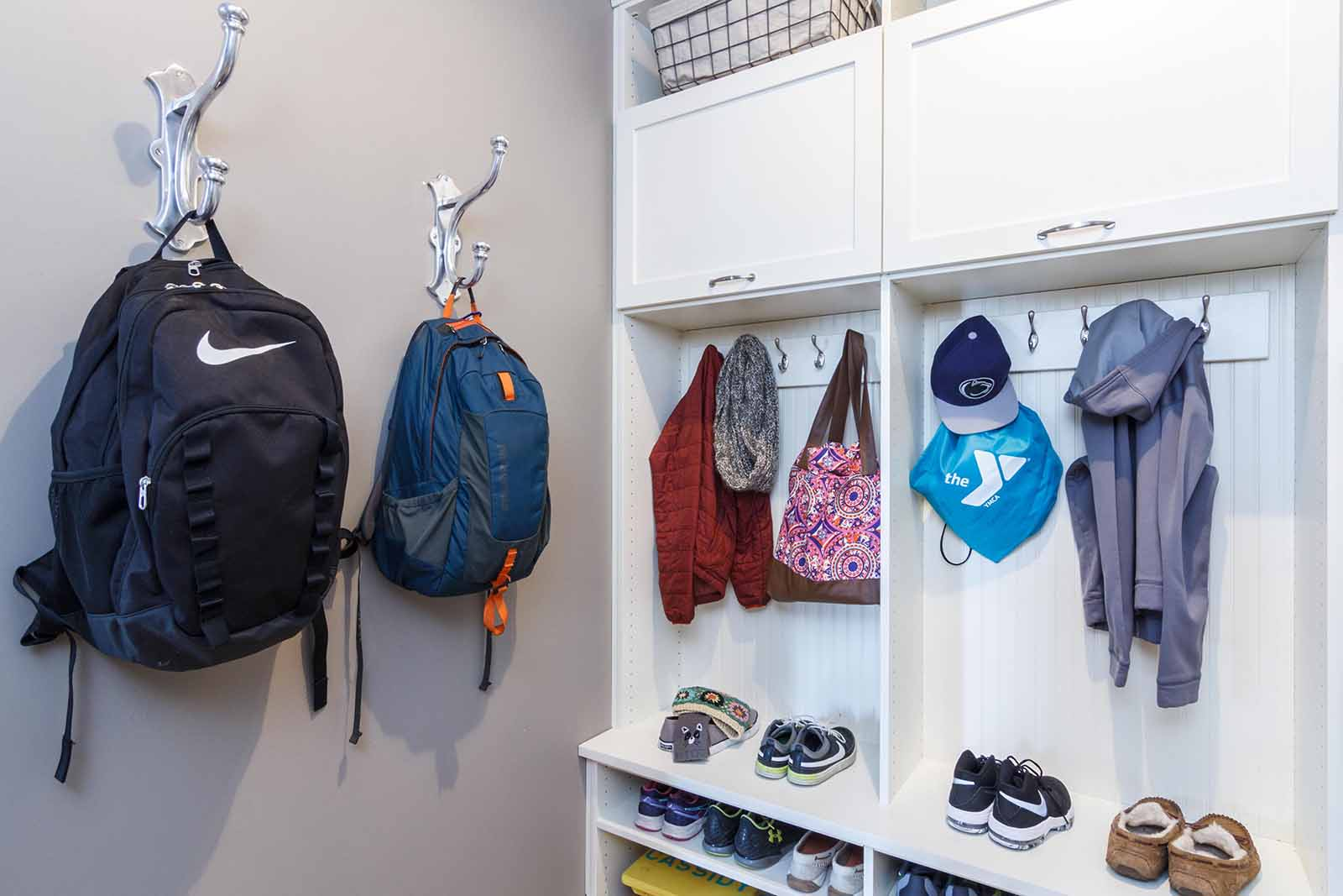 Mudroom neatly organized with backpacks hanging on hooks