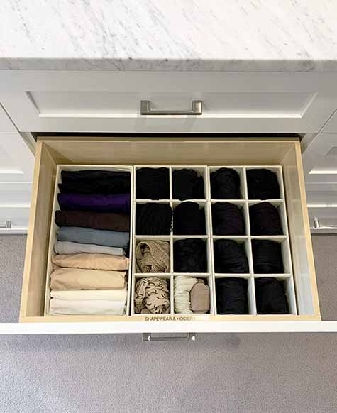 Closet drawer with hosiery organized in drawer inserts