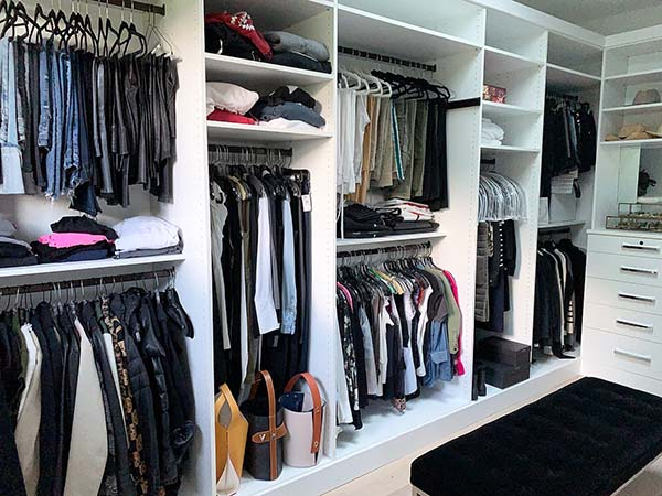 Walk In Closet with clothing organized