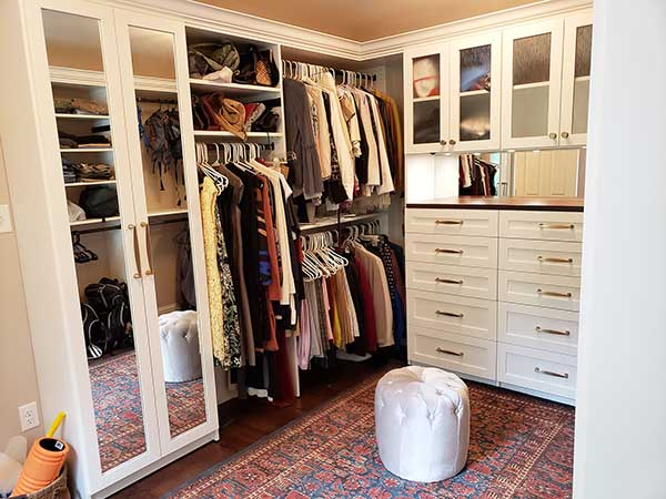 Posh walk-in closet and sitting room neatly organized
