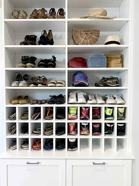 Footwear neatly organized on closet shelving and cubbies